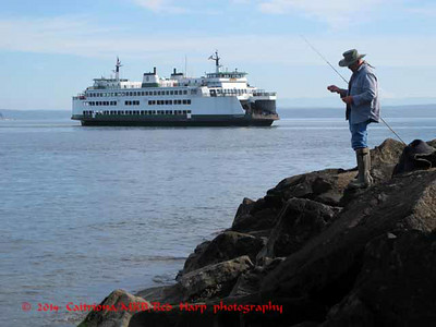 Mukilteo beach with fisherman and ferry in the background