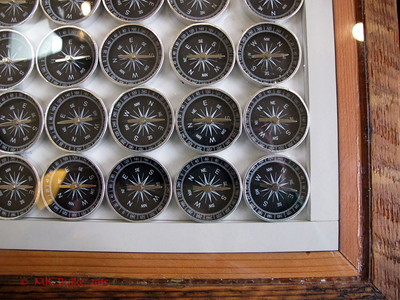 cafe tables contain displays; this one is an entire table full of compasses