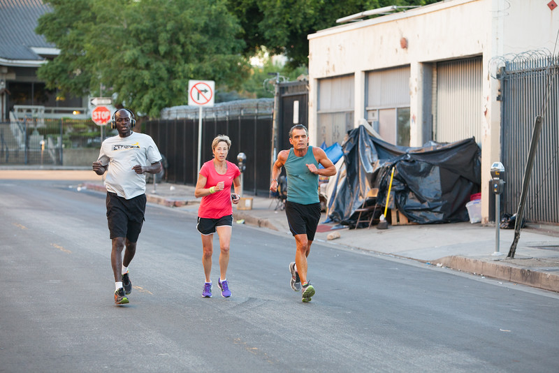 FAVORITE ****  Skid row resident Mody Diop (left), Gabi Hayes (Skid Row Marathon producer), and Judge Craig Mitchell run through the streets of L.A.'s skid row.
