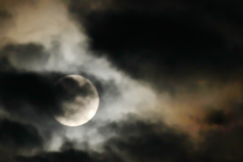 Blood Moon Shines Through Dark Clouds