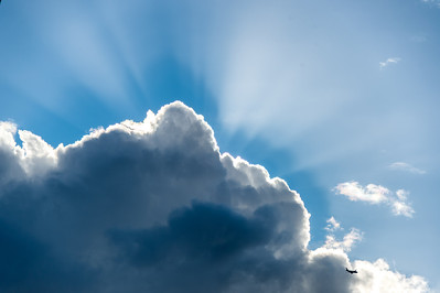 Crepuscular rays around cloud and jet plane