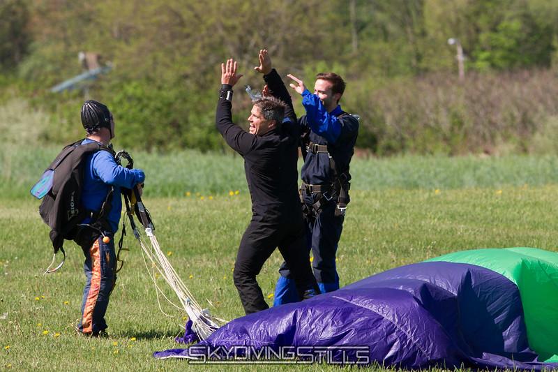 Alex receives scavenger hunt points for high fiving a tandem student after landing.