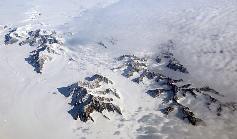 Mountains nearly submerged in thick ice, east-central Greenland