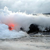 Ocean entry of red-hot lava flow at newly formed rocky cliffs along the southern shore of Big Island, Hawaii