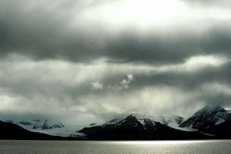 Layered skies over the Finsterwalder glacier and adjacent mountains along the southern Van Keulenfjorden, Svalbard