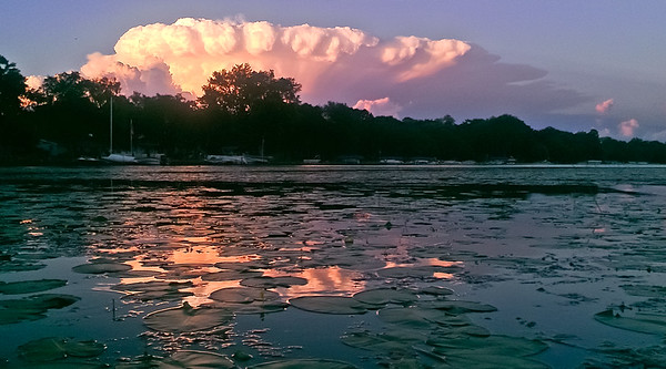 A distant storm captures some golden sunlight and reflects  it off the water