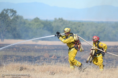 Firefighters battle a grass fire of approx. 100 acres that may have been sparked by a trailer tire that came off of a boom lift along Skyway just outside of Chico, Calif. Friday June 16, 2017. (Bill Husa -- Enterprise-Record)