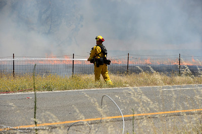 Cal Fire-Butte County's Engine 44 firefighter Dustin Topp battles a blaze that scorches several acres Friday, July 22, 2016, near Butte Creek and the Skyway in Chico, California. The fire began when a tractor trailer knocked power lines down. (Dan Reidel -- Enterprise-Record)
