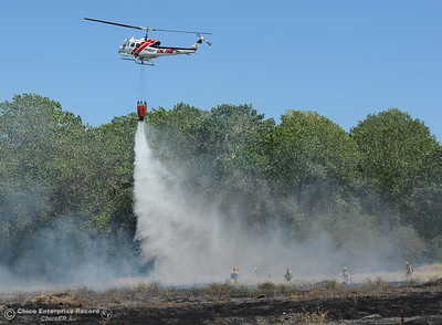 A Cal Fire helicopter drops water near a hand crew as a fire scorches several acres Friday, July 22, 2016, near Butte Creek and the Skyway in Chico, California. The fire began when a tractor trailer knocked power lines down. (Dan Reidel -- Enterprise-Record)