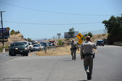 California Highway Patrol officers control traffic as a fire scorches several acres Friday, July 22, 2016, near Butte Creek and the Skyway in Chico, California. The fire began when a tractor trailer knocked power lines down. (Dan Reidel -- Enterprise-Record)