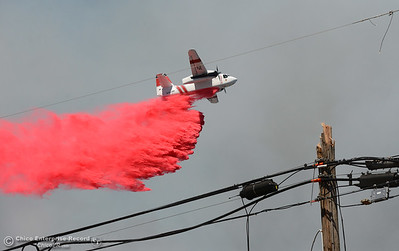 A Cal Fire plane drops retardant on a fire that scorches several acres Friday, July 22, 2016, near Butte Creek and the Skyway in Chico, California. The fire began when a tractor trailer hit this pole and knocked power lines down. (Dan Reidel -- Enterprise-Record)