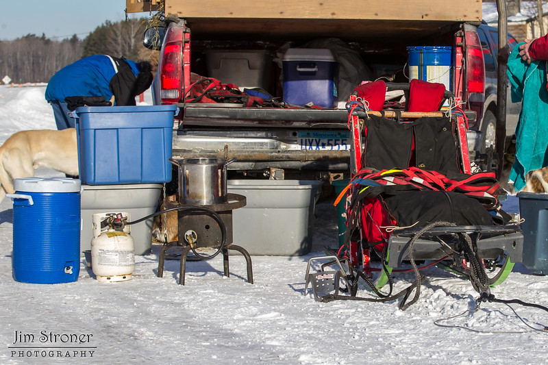 Linus Meyer preparing food for his team before the start of the Mid-Minnesota 150 sled dog race