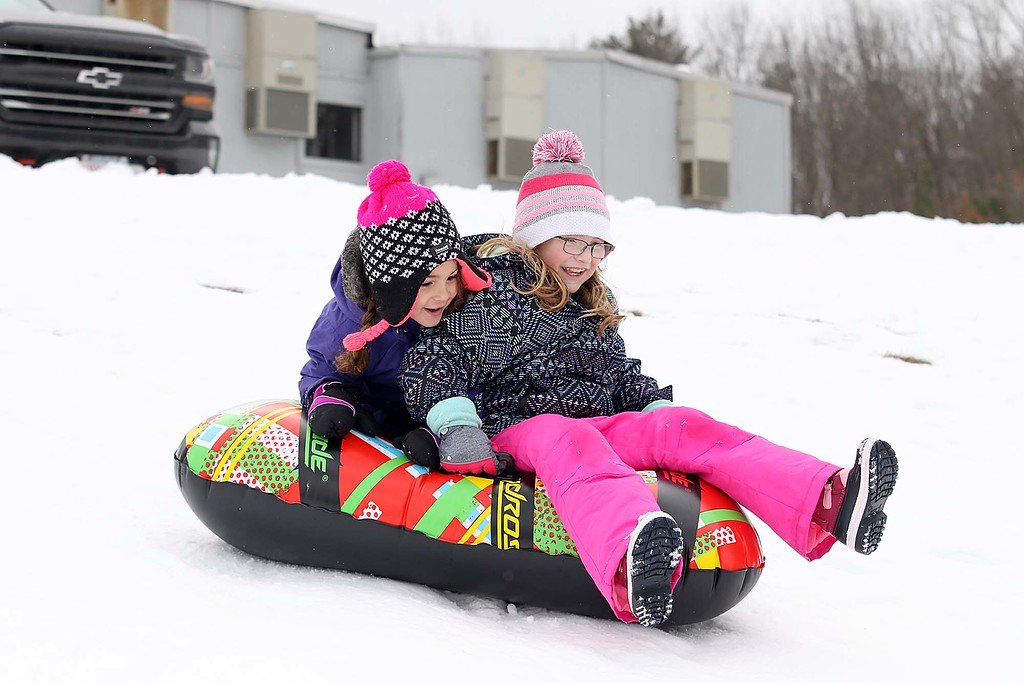 . Ava Landry, 5, sits behind Kemri Ptak, 7, both from Leominster as they enjoyed sledding down the hill next to Frances Drake Elementary School in Leominster on Saturday.  SENTINEL & ENTERPRISE/JOHN LOVE