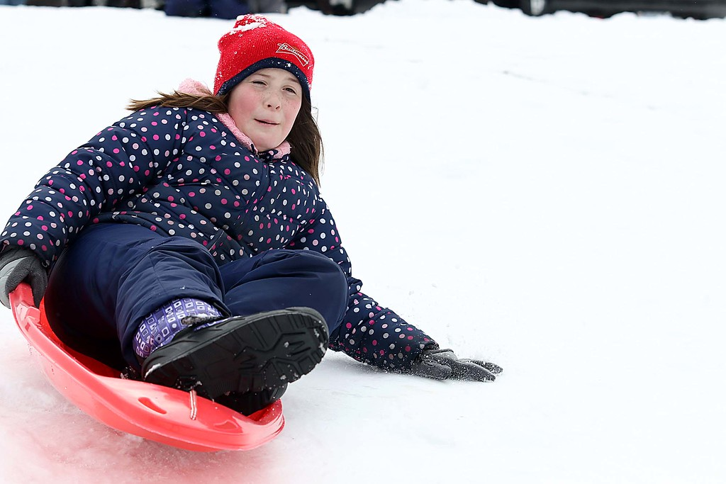 . Sarah Peterson, 10, from Fitchburg enjoyed sledding down the hill next to Frances Drake Elementary School in Leominster on Saturday.  SENTINEL & ENTERPRISE/JOHN LOVE