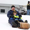 Declan hartung, 6, and his dad Jim Hartung from Leominster use a toboggan as they enjoyed sledding down the hill next to Frances Drake Elementary School in Leominster on Saturday.  SENTINEL & ENTERPRISE/JOHN LOVE