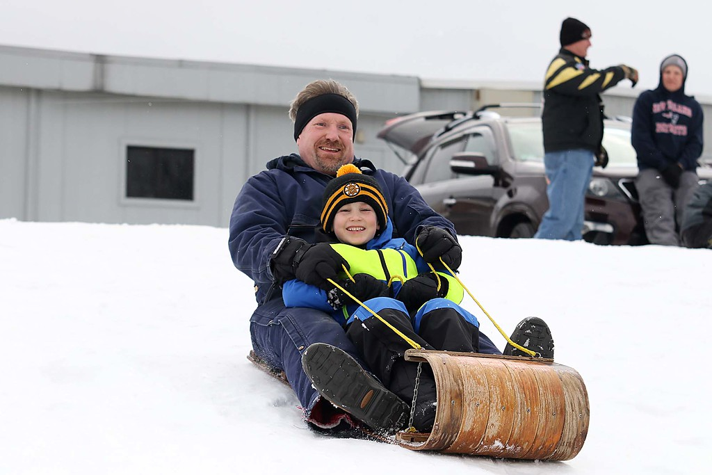 . Declan hartung, 6, and his dad Jim Hartung from Leominster use a toboggan as they enjoyed sledding down the hill next to Frances Drake Elementary School in Leominster on Saturday.  SENTINEL & ENTERPRISE/JOHN LOVE