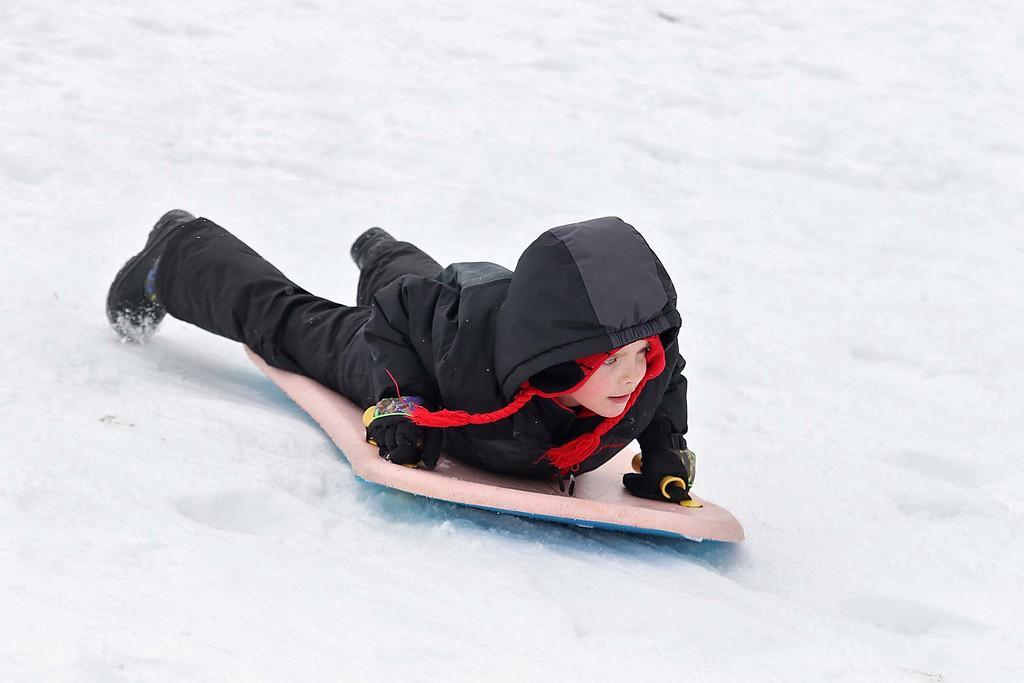 . Cooper Landry, 7, from Leominster enjoyed sledding down the hill next to Frances Drake Elementary School in Leominster on Saturday.  SENTINEL & ENTERPRISE/JOHN LOVE