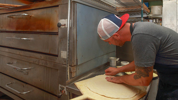 A pizza maker is tossing the dough.