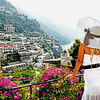 Backside View of a Woman in White Summer Dress and Hat Looking Out on a Balcony, Positano, Campania, Italy