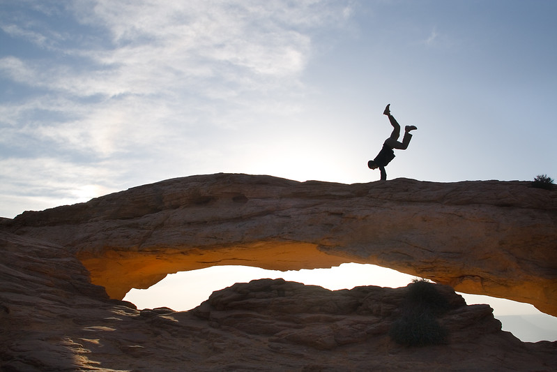Model Released, Man doing a Handstand on Mesa Arch, Canyonlands National Park, Utah, USA, North America