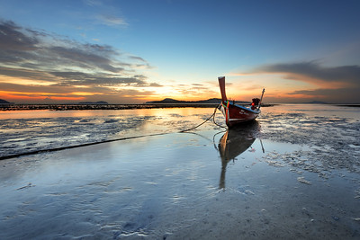 Thai long tail boat at sunrise during low tide, Rawai Beach
