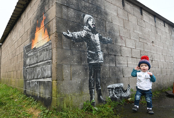 "New Banksy artwork appeared on the back of a garage block in Port Talbot.<br /> <br /> Iestyn Paxton aged 16 months from Taibach admiring the new Banksy art work.<br /> <br /> Copyright © 2018 by Adrian White <br /> Photography, all rights reserved.<br /> For permission to publish - contact me<br /> via  <a href=""http://www.adrianwhitephotography.co.uk"">http://www.adrianwhitephotography.co.uk</a><br /> Please respect copyright laws."