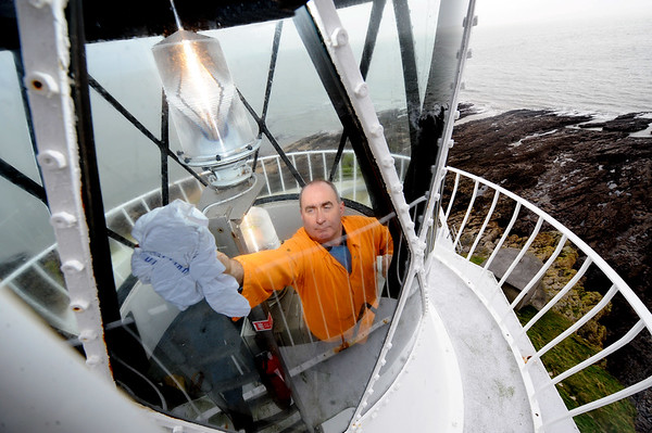 SWANSEA / CAPTION ONLY<br /> Monday 9th January 2012<br /> Mumbles Lighthouse attendant Paul Thomas polishing the windows of the 216 year old structure 35 metres above sea level. The husbandry visit by Trinity House personel to carry out basic maintenance and cleaning of the facility takes place quarterly, and following the storms of last week the lighthouse will now be ready to guide ships away from Mumbles Head in the future months.<br /> <br /> Contact. Paul 07969 181017