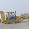 PAUL BILODEAU/Staff photo. <br /> Workers build up sand barriers as Hurricane Sandy moves in at Seabrook Beach.