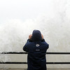 PAUL BILODEAU/Staff photo. <br /> A storm watcher gets up close to waves crashing over the seawall at Hampston Beach as Hurricane Sandy moves in.