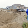 PAUL BILODEAU/Staff photo. <br /> Richard Mahoney of climbs over a sand barrier at Seabrook Beach as as Hurricane Sandy moves in.