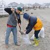 PAUL BILODEAU/Staff photo. <br /> Matt Fauvel, left, and Ann Coyne fill sandbags at Hampton Beach as Hurricane Sandy moves in.