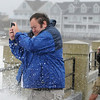 PAUL BILODEAU/Staff photo. <br /> Storm watchers take photos from their smartphones as Hurricane Sandy moves in at Hampton Beach.