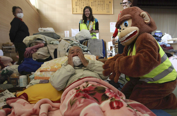 A volunteer staff member in costume peps up a displaced people at a shelter near the area devastated by the March 11 tsunami in Rikuzentakata, Iwate Prefecture, Japan, Thursday, April 7, 2011. (AP Photo/Yomiuri Shimbun, Tsuyoshi Matsumoto)