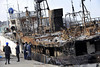 Fishermen hang around a pier as a burnt tuna boat is anchored in the area devastated by the March 11 tsunami in Kesennuma, Miyagi Prefecture, Japan, Thursday, April 7, 2011. (AP Photo/Yomiuri Shimbun, Manabu Kato)