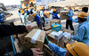 Workers receive relief goods at their damaged factory by the March 11 earthquake and tsunami,  in Ofunato, Iwate prefecture, Japan, Thursday, April 7, 2011. (AP Photo/Lee Jin-man)