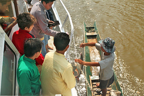 Captain buys a fish from hill tribe fishermen