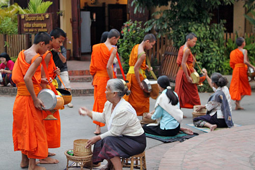 Locals give alms in front of their houses