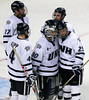 New Hampshire's Mike Beck (25) hugs goalie Matt Di Girolamo (30) next to Damon Kipp and Paul Thompson (17) after losing 4-1 to Merrimack in the third period of a Hockey East tournament semifinal hockey game, Friday, March 18, 2011, in Boston. (AP Photo)