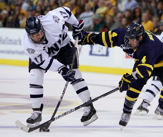 New Hampshire's Paul Thompson (17) takes a shot on goal under the stick of Merrimack's Jordan Heywood (4) in the second period of a Hockey East tournament semifinal hockey game, Friday, March 18, 2011, in Boston. (AP Photo)