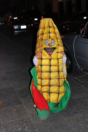 "Child dresses as ""Little Elote"" - an ear of corn - to help at the family food cart"