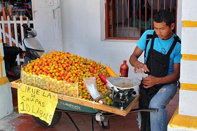 Vendor selling ciruelas, a tiny plum-like fruit