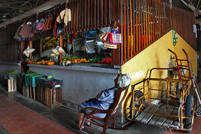 Woman naps in front of her market stall