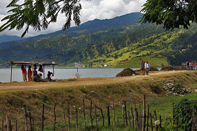 A rough dirt path parallels the shoreline of Phewa Lake