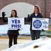 Debbi Leuteritz, left, and Kristen Michaud, hold signs in support of Warrant Article #1 as they campaign outside Pelham High School.  Both women have middle-school aged kids who would benefit from improvements to the high school.  Photo by Mary Schwalm