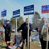Selectmen candidates Scott Mitchell, from left,Craig Schuster and Harold Morse wave to voters as they pull into the polls at the Atkinson Community Center on Tuesday. Photo by Ryan Hutton.