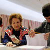 Marie Leone, left, checks the photo ID against the register with Nicholas Santo, 18, as a voter checks in at Rockingham Park in Salem. Photo by Mary Schwalm