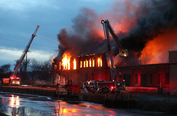 Firefighters battle a 5-alarm fire at the Merrimac Paper Co. at So. Canal Street in Lawrence. Photo by Mary Schwalm