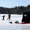 Ashlynn Fuller, 7, left, and Lorelei Fuller, 6, run with their dad Jeremy Fuller, of Haverhill, to a sprung flag at a hole during the Haverhill Hound Rod & Gun Club's 2014 Ice Fishing Derby on Chadwick Pond in Haverhill.  Photo by Mary Schwalm