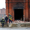 State Fire Investigators walk along the brick scattered foundation at the Merrimac Paper Co. in Lawrence. Photo by Mary Schwalm