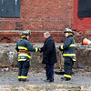 Lawrence Mayor Daniel Rivera, center, shakes hands with a Lawrence firefighter after meeting with them on the scene Tuesday morning at the multi-alarm fire. Photo by Mary Schwalm